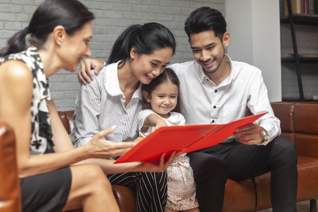 Happy young Asian family sitting on couch and talking with family counselor or meeting real-estate agent for house investment. Multiethnic family meeting a financial agent or bank worker offers loan